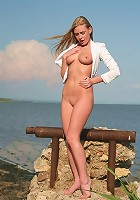Busty blonde takes off her jacket and panties on the beach