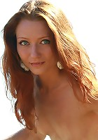 Natural petite redhead teen posing naked in the field