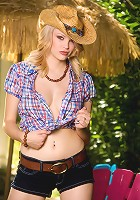 Foxy blonde cowgirl showing her weapons