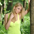 Zemani.com Druida - Pretty girl with a face of an angel in yellow blouse shows everything on the green fresh grass in a forest.
